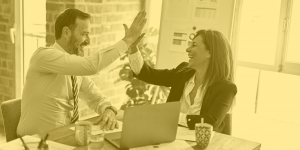 Two co-workers, one male, one female, high fiving around a meeting table. A yellow filter has been laid over the image.